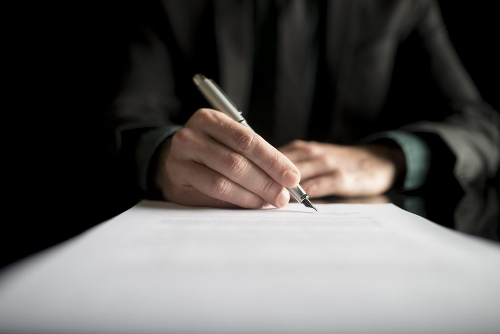 Closeup of lawyer or executive signing a contract